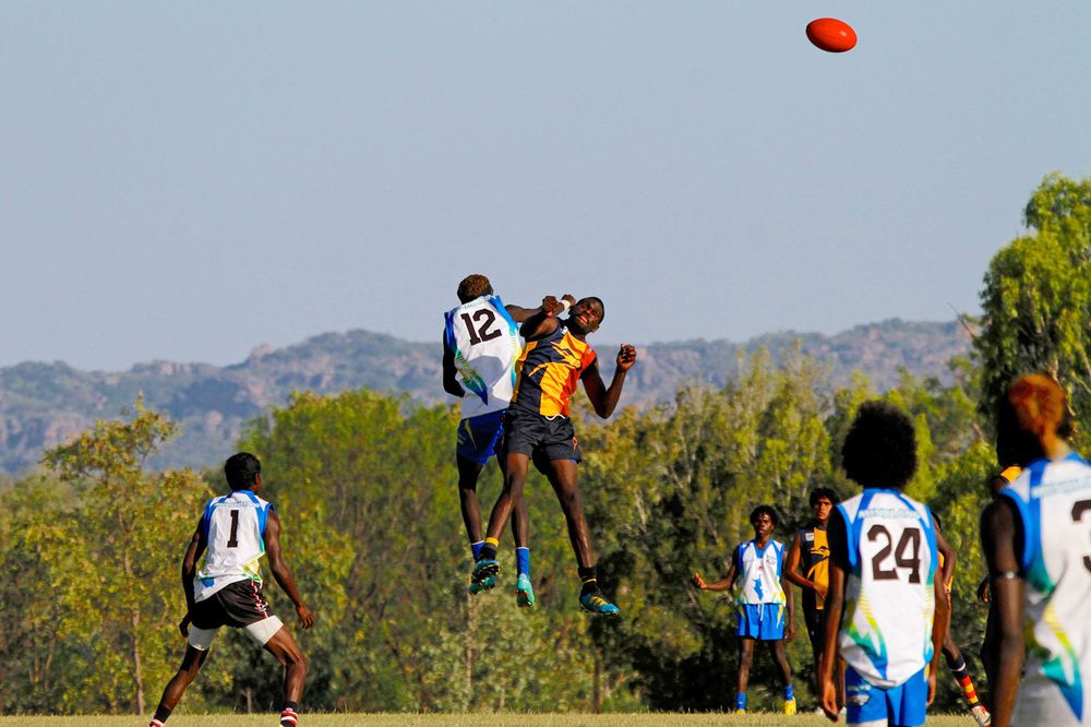 The Minjilang Eagles (in blue and white) compete in the ruck against St John's in the 2013 Gurrung Sports Carnival.