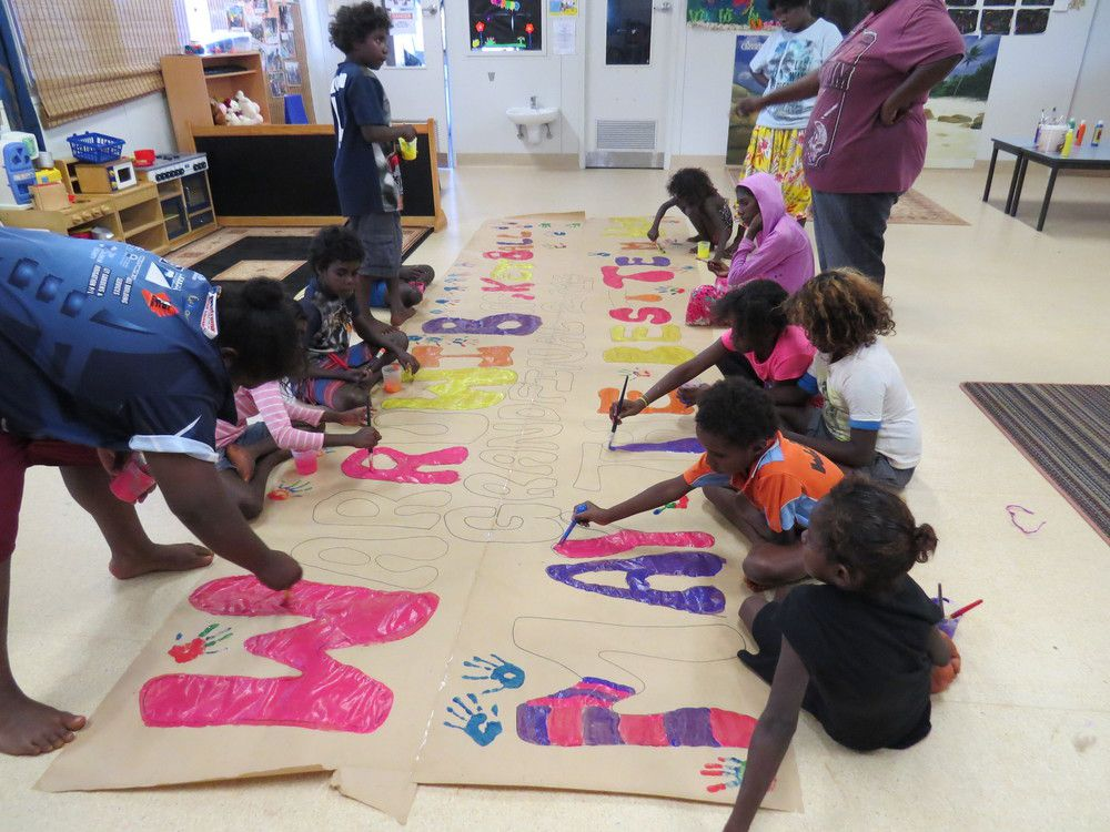 Kids at the Warruwi creche create a huge banner for the basketball finals event.